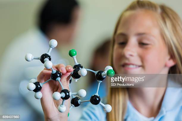 Confident schoolgirl with atomic structure model