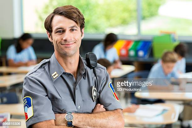 Confident security officer in front of class of children