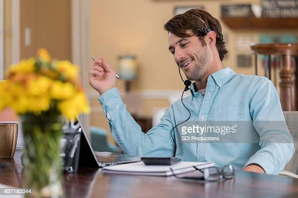 Confident self employed man uses a headset in home office