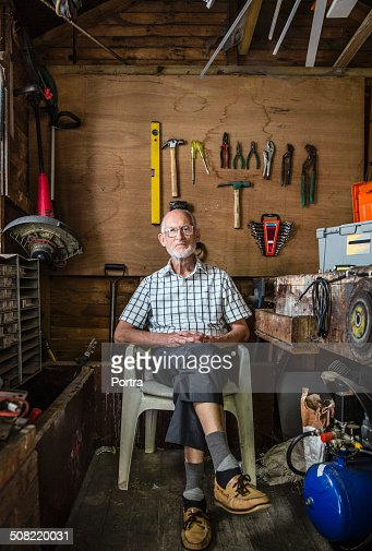 Confident senior carpenter sitting in workshop
