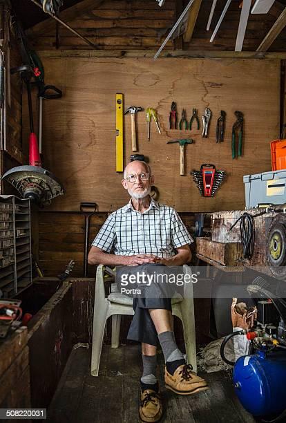 Confident senior carpenter sitting in workshop