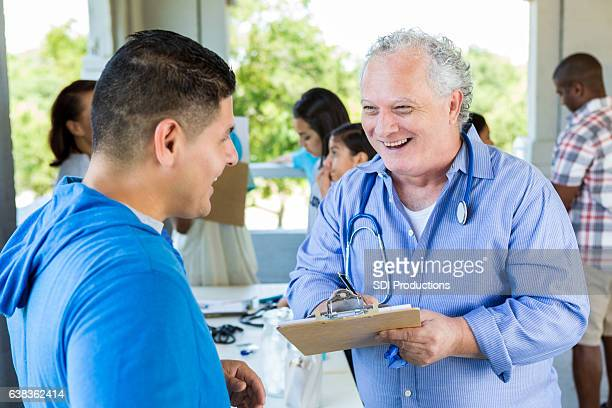 Confident senior doctor talks with patient at free outdoor clinic