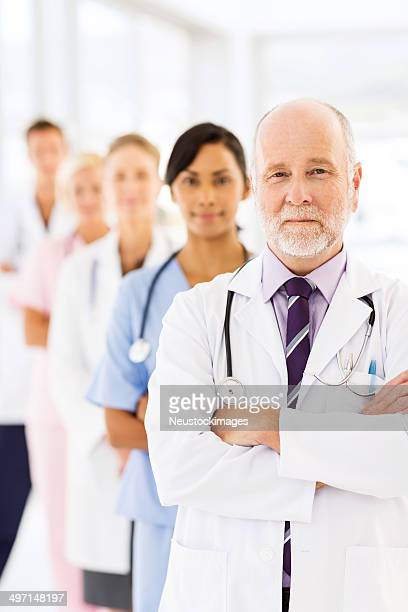 Confident Senior Doctor With Row Of Medical Team