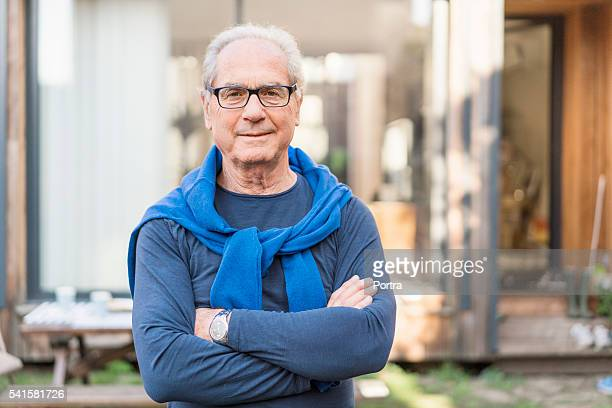 Confident senior man with arms crossed in backyard
