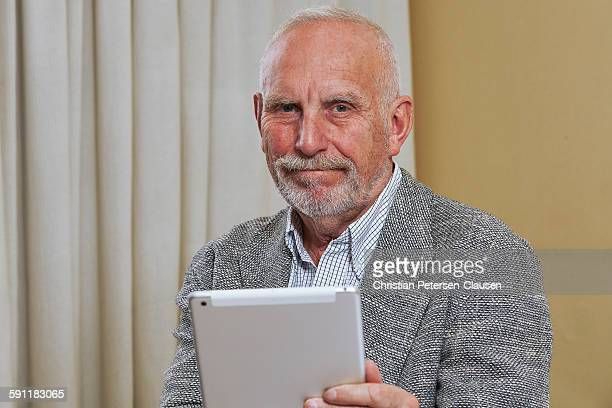 Confident senior manager using tablet computer
