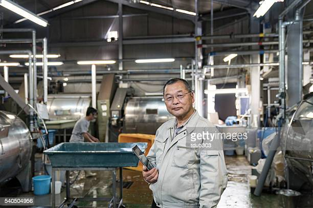Confident senior textile industry manager holding a digital tablet