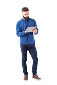 Confident serious bearded business man using tablet touch pad screen. Full body isolated on white background.