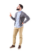 Confident stylish hipster business man pointing finger up and looking above. Full body length portrait isolated on white studio background.