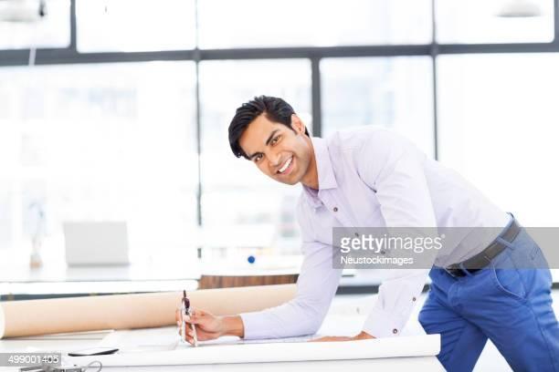 Confident Surveyor Working On Blueprint In Office
