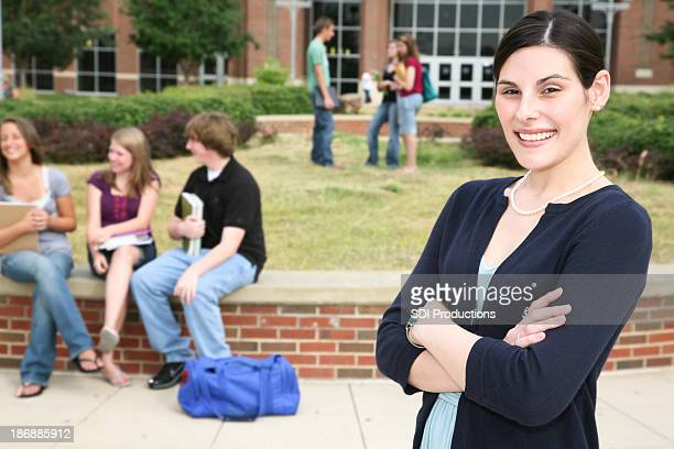 Confident Teacher Standing Outside School in front of Students
