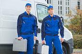 Full length portrait of confident technicians standing against truck on street