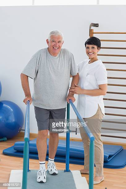 Confident trainer with man walking on parallel bars