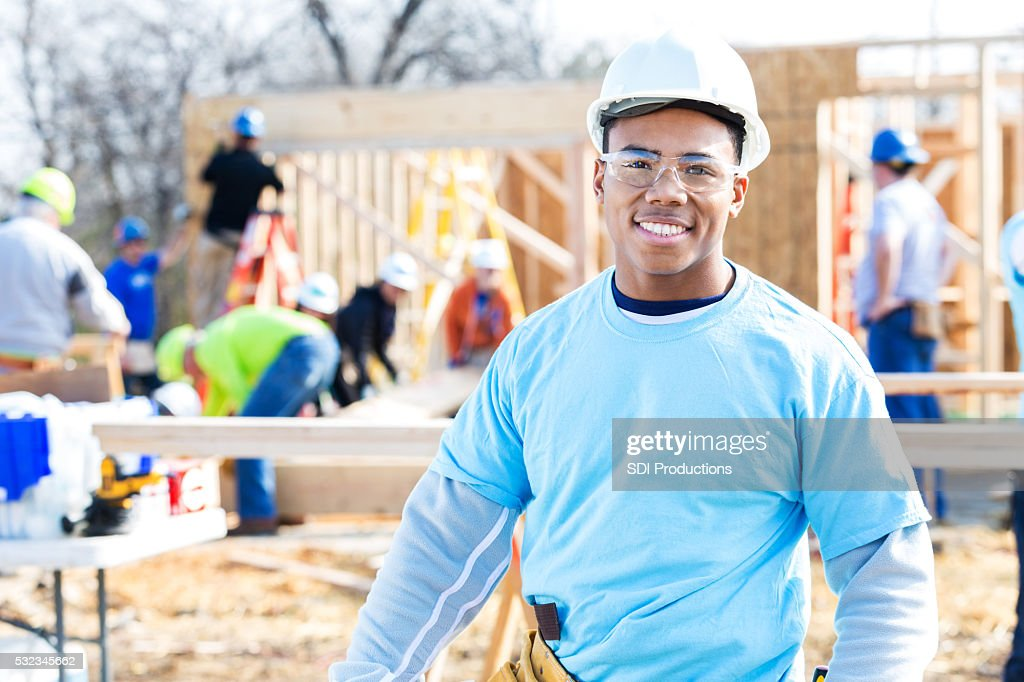 Confident volunteer construction foreman at work site : Stock Photo