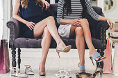 Part of young women with perfect legs keeping their legs crossed at knee while sitting on sofa at the shoe store