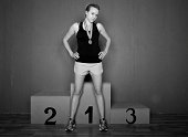 Confident woman athlete in front of winners podium