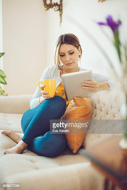 Confident woman drinking coffee and reading a tablet