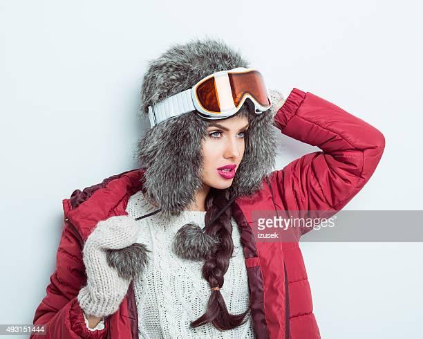 Confiant femme en tenue d'hiver, en fourrure casquette et lunettes