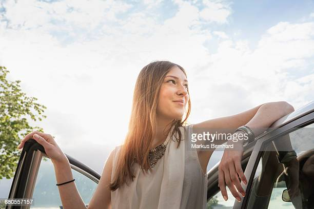 Confident woman leaning at her new car