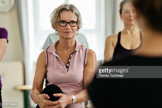 Confident woman looking at instructor while exercising in gym