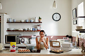 Confident woman preparing cupcakes in kitchen