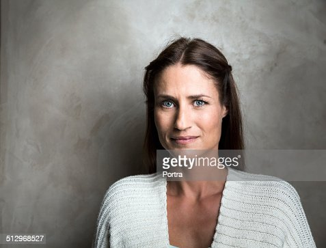 Confident woman smiling against wall