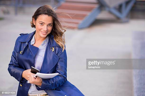 Confident woman smiling and holding documents and smartphone out
