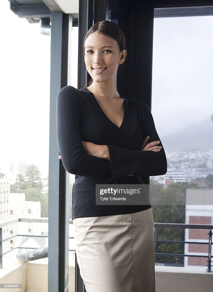 Confident woman smiling standing in her office : Stock Photo