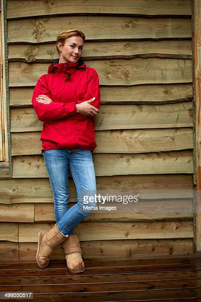 Confident woman standing against wooden wall