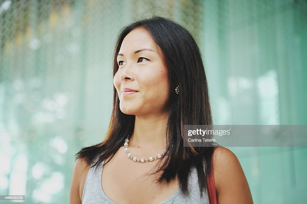 Confident woman stands outside glass office tower : Stock Photo