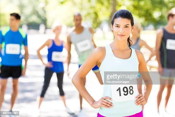 Zuversichtlich Frau mit Konkurrenten im Hintergrund vor dem Marathon