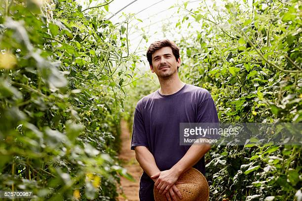 Confident worker standing in greenhouse