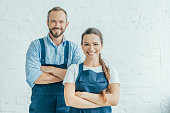 confident workers in overalls posing with crossed arms