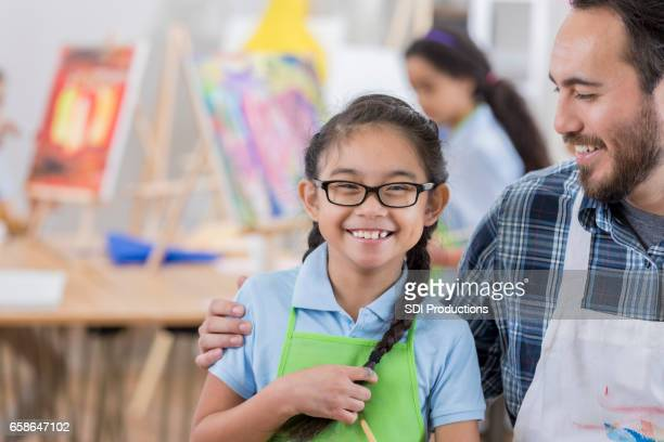 Confident young artist with teacher
