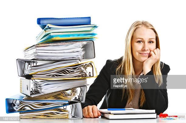 Confident young blonde businesswoman smiles despite huge workload