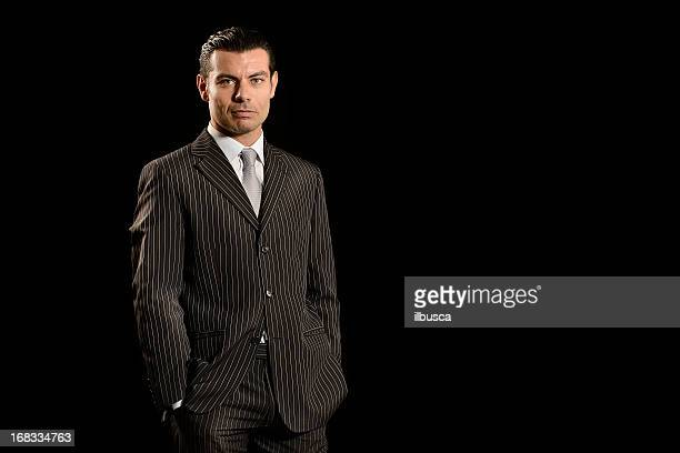 Confident young businessman on black background