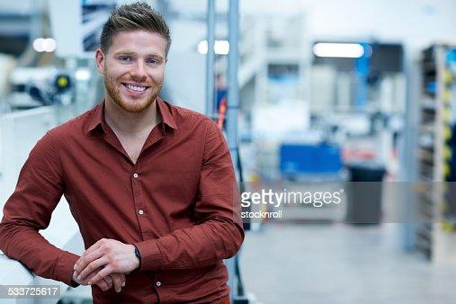 Confiant jeune homme d'affaires debout dans l'usine