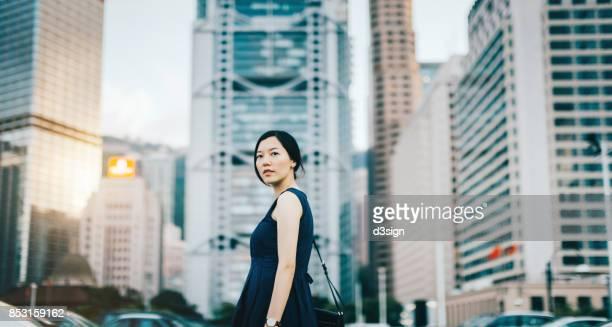 Confident young businesswoman against urban cityscape with highrise corporate buildings in financial district in Hong Kong