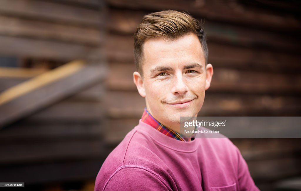 Confident young Englishman portrait in front of wooden wall : Stock Photo