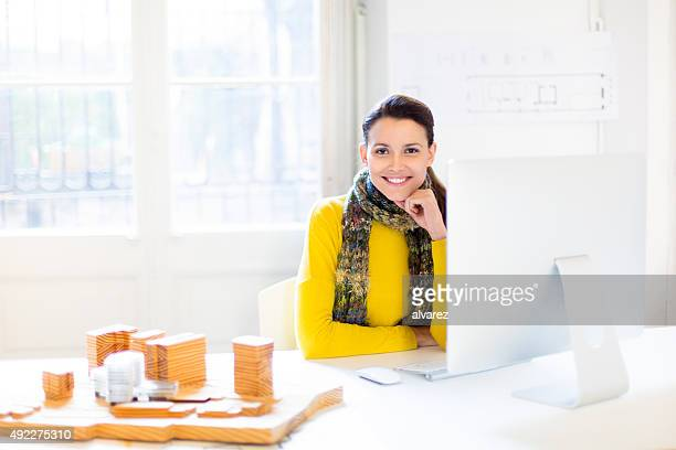 Confident young female architect at her desk