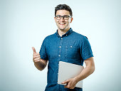Confident young handsome man in shirt holding laptop while standing against white background