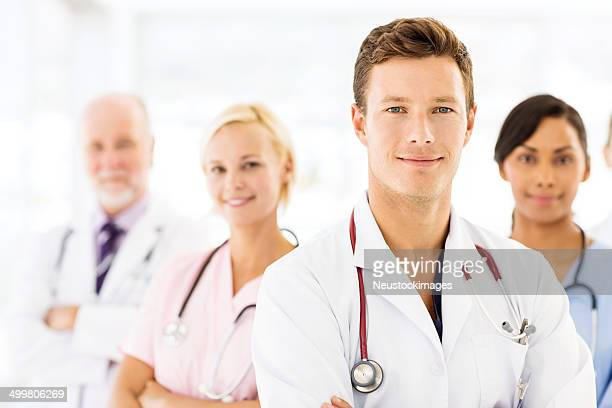 Confident Young Male Doctor With Medical Team