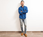 Full length portrait of a young and confident Hispanic man standing against a white wall with his arms crossed and smiling