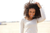 Close up portrait of a confident young woman smiling outdoors