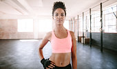 Portrait of confident young woman standing in gym. African female fitness model looking at camera.