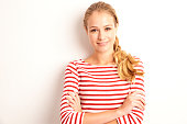 Portrait shot of beautiful young woman wearing striped shirt while looking at camera and standing at isolated white background.
