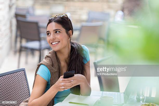 Confident young woman with smart phone at outdoor cafe