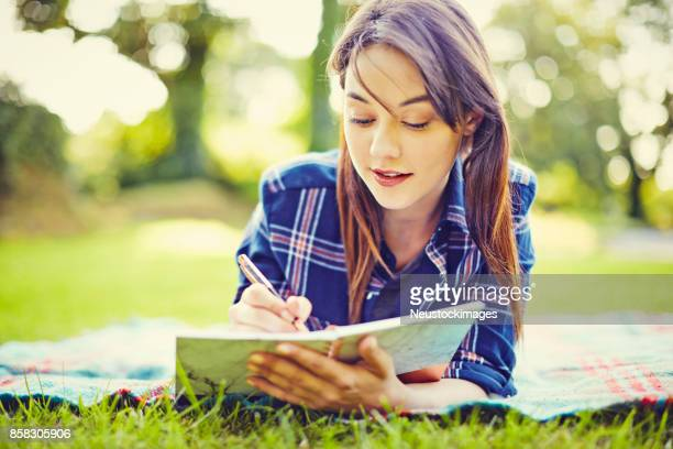 Confident young woman writing in diary while lying at park
