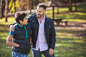 Father and son walking together and having confidential conversations