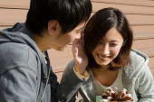 young couple talk confidentially in sunny outside. a woman has a box with ribbon, a man talk to her closely, they look chummy.