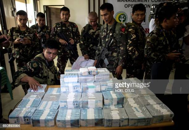 Confiscated cash and cheques amounting to 16 million USD are shown by Philippine military personnel during a press conference at the provincial...
